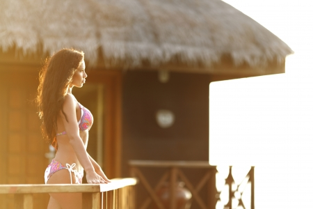 Woman standing near fence of tropical hotel Stock Photo - 18229950
