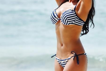 바다 배경에 비키니 입은 젊은 섹시 한 여자