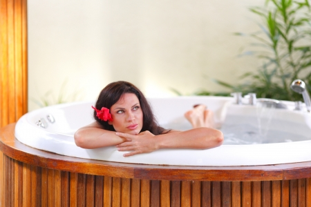Pretty woman relaxing in jacuzzi of tropical hotel photo