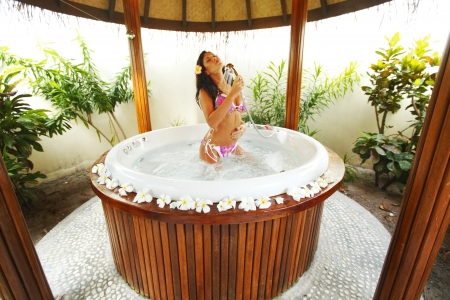 jacuzzi: Pretty woman relaxing in jacuzzi of tropical hotel