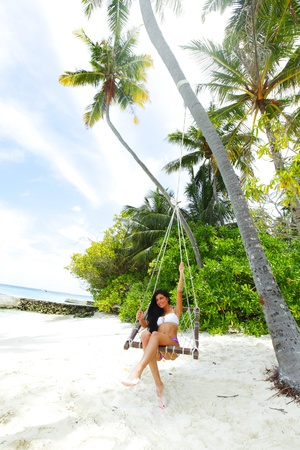 Beautiful woman swinging in beach hammock photo