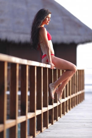 Woman in red bikini sitting on fence near tropical hotel Stock Photo - 18522615