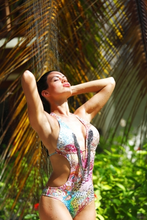 Sexy woman in tropical shower and palms around photo