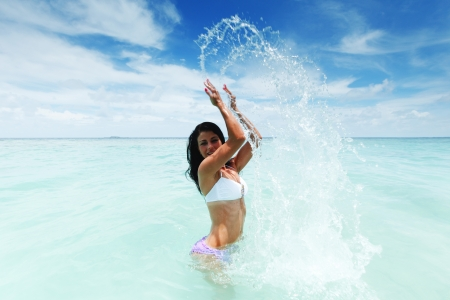 Cheerful pretty young woman splashin in sea