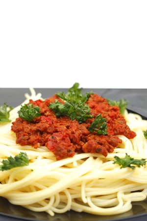 Spaghetti bolognese on black plate close-up photo