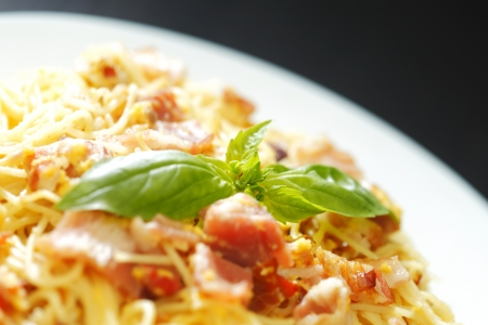 Spaghetti carbonara with fried bacon in plate on black table photo