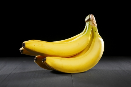 Fresh bananas on black background photo