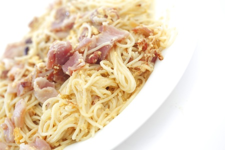 Spaghetti carbonara with fried bacon on white background photo