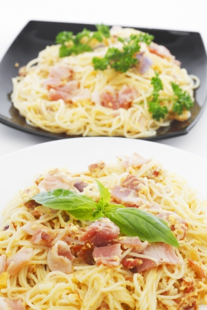 Spaghetti carbonara with fried bacon in two plates on white background photo