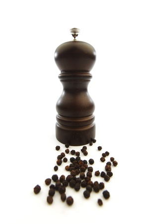 Wooden peppermill with peppercorns isolated on white background photo