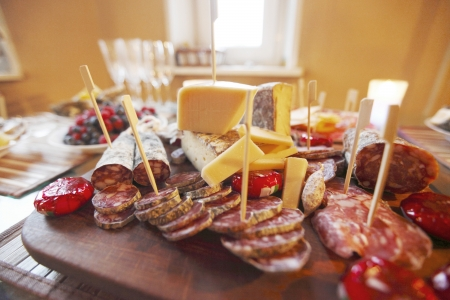 Various sliced sausage and cheese on table photo