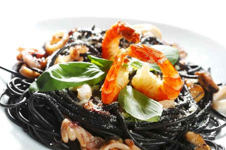 Black spaghetti with seafood isolated on white background photo