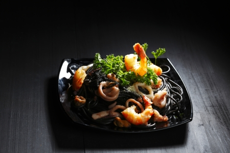 Black spaghetti with seafood on black table photo