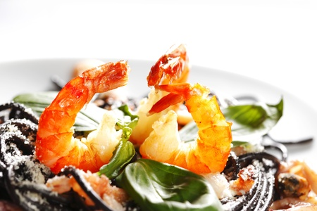 black dish: Black spaghetti with seafood isolated on white background