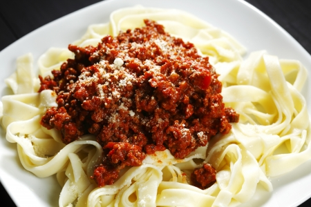 Spaghetti bolognese with parmesan cheese in white plate on black table