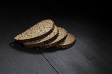 Sliced black bread on wooden table close-up photo