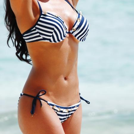 Young sexy woman in bikini on sea background