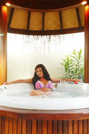 Pretty woman relaxing in bathtub of tropical hotel photo