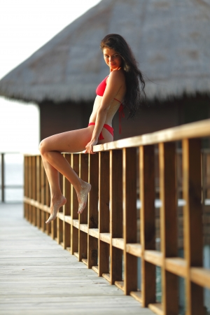 Woman in red bikini sitting on fence near tropical hotel Stock Photo - 19687243