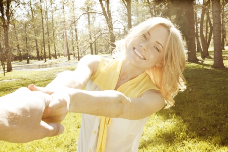 Happy woman holding by hands and whirling in park photo