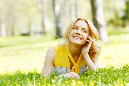 Happy young woman lying on grass photo