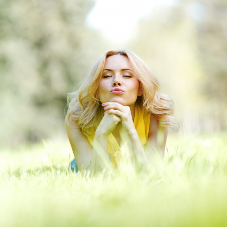 girl blowing: Happy young woman lying on grass and blowing kiss