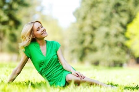 Happy young woman sitting on grass photo