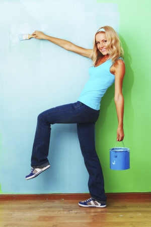woman paints the wall brush photo