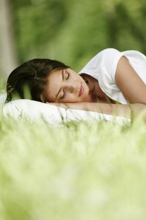 sono: Jovem, mulher, dormindo no travesseiro macio na grama da mola fresca