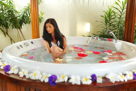 Pretty woman relaxing in jacuzzi with flower petals photo
