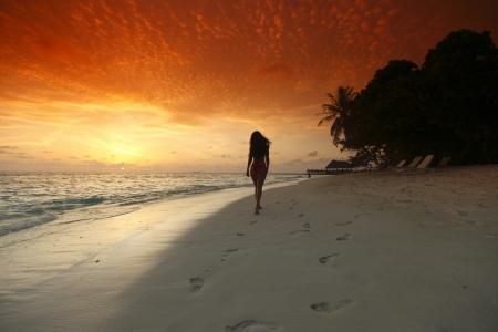 walking alone: Mujer joven caminando en la playa bajo la luz del atardecer