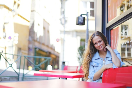 beautiful young woman sitting alone in street cafe photo