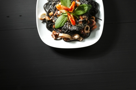 black dish: Black spaghetti with seafood on black table