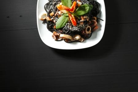 spaghetti saus: Zwarte spaghetti met zeevruchten op zwarte lijst Stockfoto