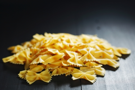 Farfalle - bow shaped dry pasta on wooden table photo