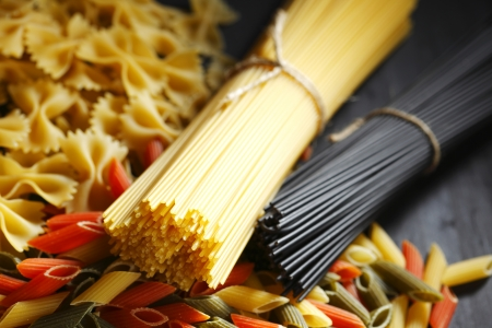 Various Italian pasta on black table photo