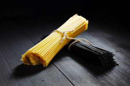 Black and white dry spaghetti on wooden table photo