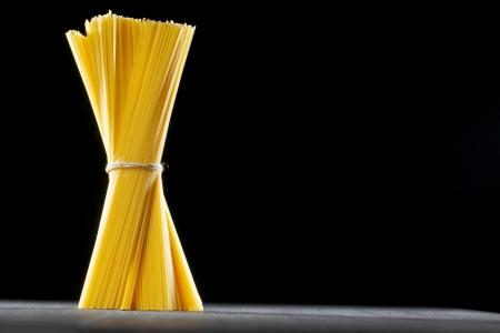 Raw pasta on black table close-up photo