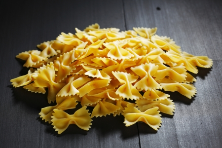 ribbon pasta: Farfalle - bow shaped dry pasta on wooden table
