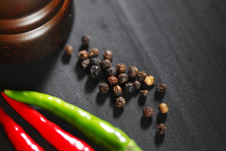 intense flavor: Wooden peppermill with pepper on black table