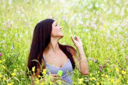 happy woman smile in green grass soap bubbles around photo