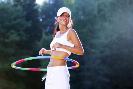 hoops: woman rotates hula hoop on nature background