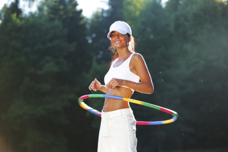 rotates: woman rotates hula hoop on nature background