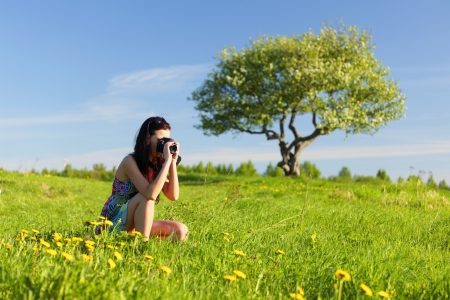 woman photographer on green grass field photo