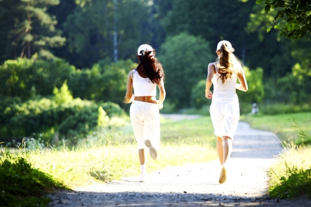 women run by sunny park alley photo