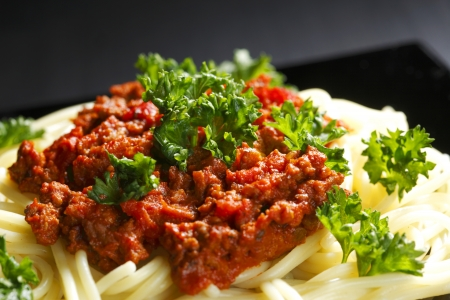 ground beef: Spaghetti bolognese in black plate on dark background