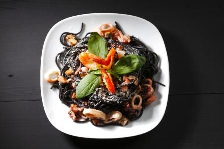 Schwarze Spaghetti mit Meeresfr?chten auf schwarzen Tisch