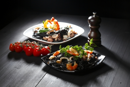 pepper castor: Black spaghetti with seafood on black table