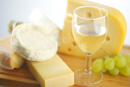 queso de cabra: queso y vino en una mesa de madera Foto de archivo