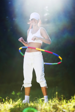 woman rotates hoop on nature background photo